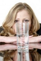 woman-looking-intensely-at-a-glass-half-full-or-half-empty-glass-of-water